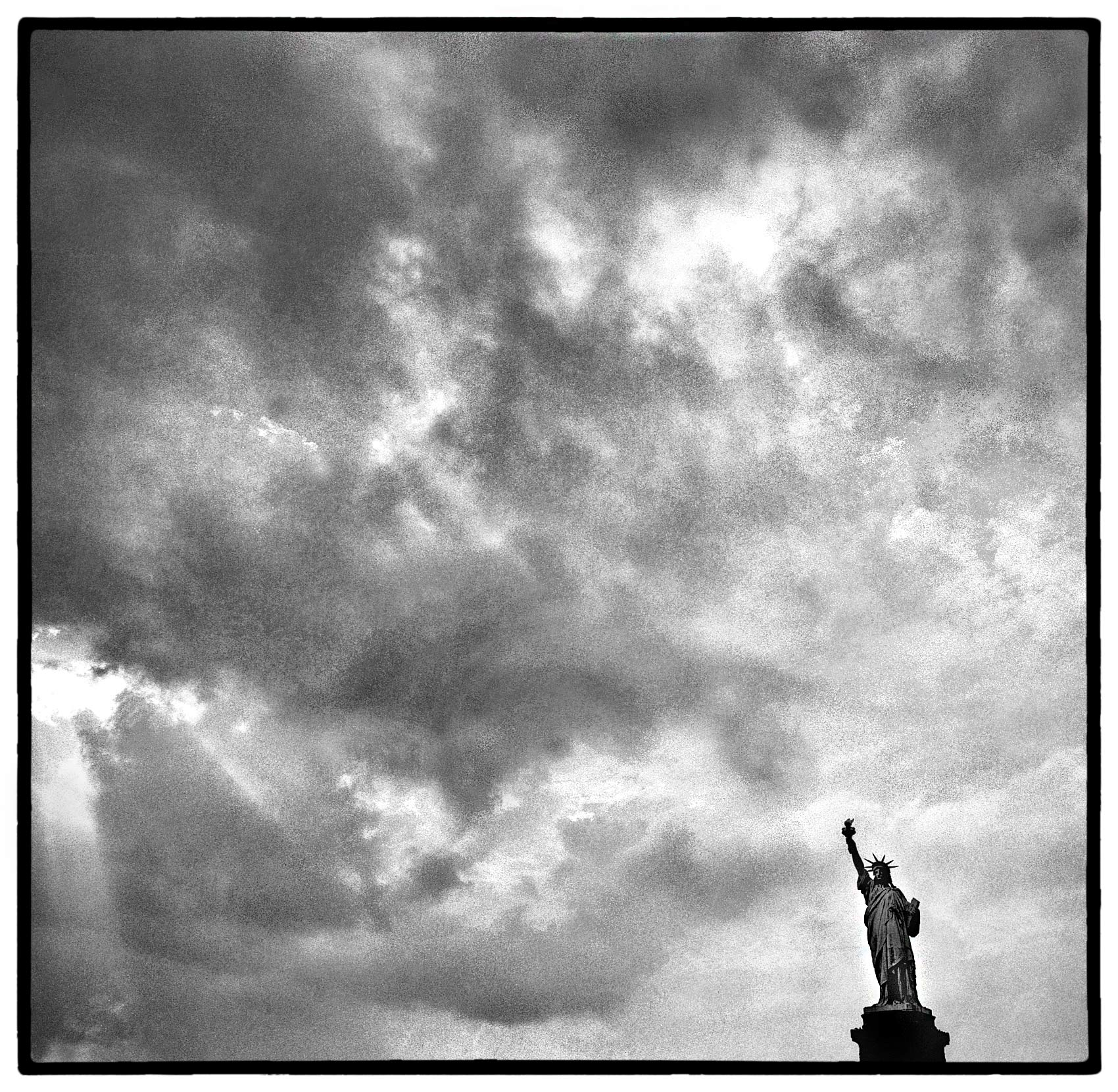 the sun breaks through the clouds over the statue of liberty in new york harbour